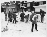 Group of ten people shoveling snow on the street by The Buffalo Courier-Express Newspaper