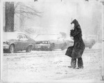 Woman shielding face in the snow by The Buffalo Courier-Express Newspaper