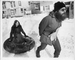 Man dragging woman on inner tube down snow covered street