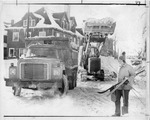 Man carrying skis in front of snow removal equipment on street by The Buffalo Courier-Express Newspaper