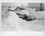 Abandoned car covered in snow