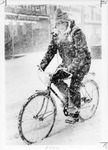 Man riding bicycle in snow storm by The Buffalo Courier-Express Newspaper
