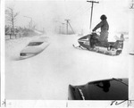 Man on snowmobile driving near abandoned cars