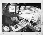 Man sitting inside a plow truck as it moves down the street by The Buffalo Courier-Express Newspaper