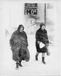 Two older women walking through the snow storm