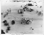 Aerial view of three homes covered by snow