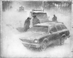 Two police officers looking into a snow covered car by The Buffalo Courier-Express Newspaper