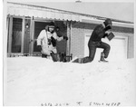 Two individuals climbing out of house covered by snow by The Buffalo Courier-Express Newspaper