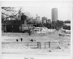 Three kids playing ice hockey with skyline in background