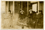Four people bundled up sitting in front of a building by The Francis Fronczak Collection