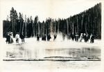 A group of people standing at a forest's edge in front of a body of water by The Francis Fronczak Collection